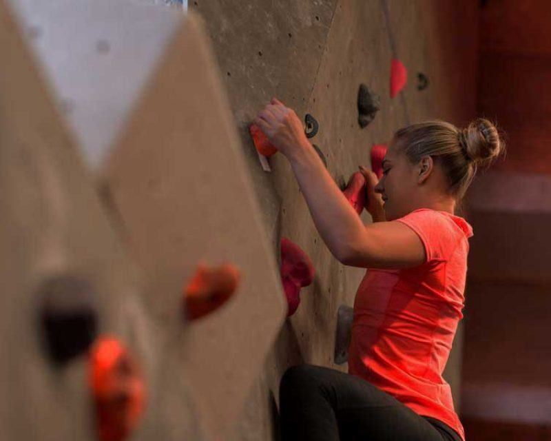 Woman climbing the wall in a gym